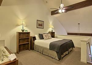The bedroom in the loft has a comfortable king sized bed, two bedside tables, a dresser, closet and TV with cable