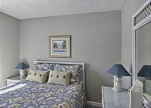 Queen size bed with dresser and TV
