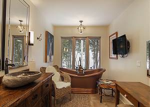 This beautiful bathroom offers custom furniture with a copper soaking tub that overlooks Lake Michigan, 2 stone sinks, flat screen TV and lighted vanity area