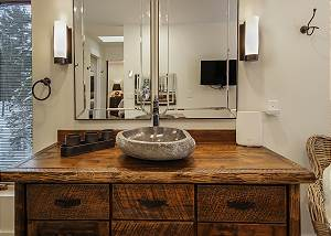 This beautiful bathroom offers custom furniture with a cooper soaking tub that overlooks Lake Michigan, 2 stone sinks, flat screen TV and lighted vanity area