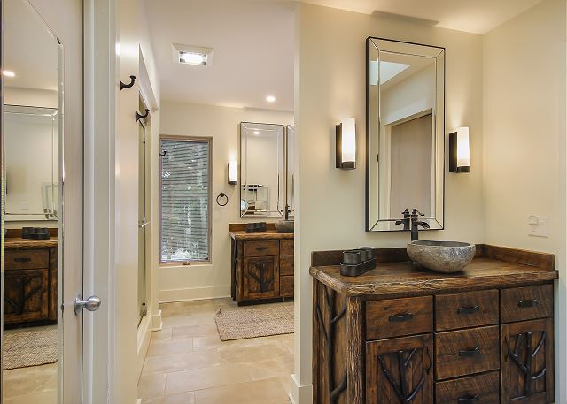 This beautiful bathroom offers custom furniture with a cooper soaking tub that overlooks Lake Michigan ,2 stone sinks, flat screen TV and lighted vanity area