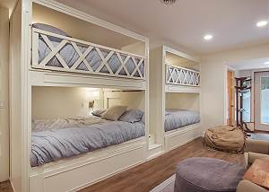 This great bunk room has stairs that go up the middle for accessing the upper bunks. Each bunk has a dedicated light, reading light and USB ports.  This is the only room with out a TV, perfect for those kids that have limited viewing time.