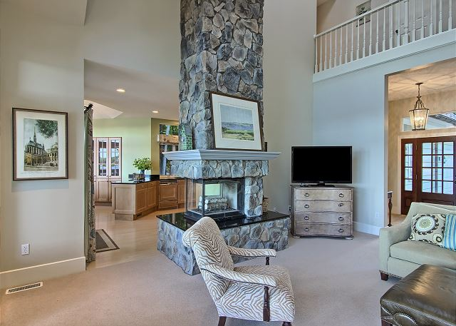view of the 2 sided fireplace, kitchen and living room