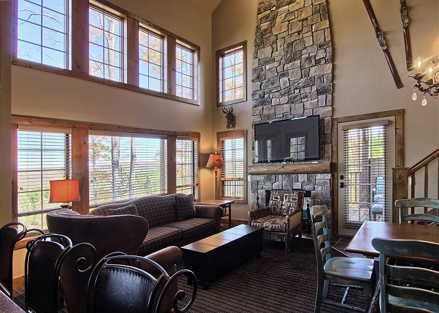 Cozy living room with beautiful floor to ceiling windows and custom stone fireplace