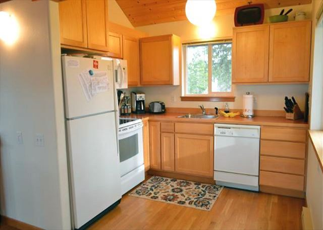 Fully stocked kitchen with dishwasher, microwave and flat top stove.