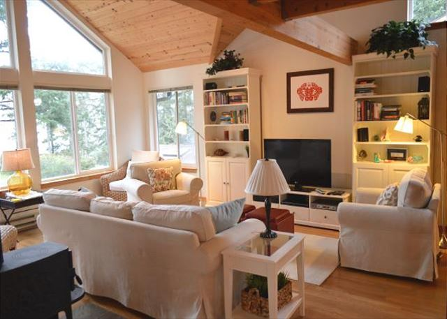 Living Room and sitting area with flat screen TV, cable, surround sound and a wood stove
