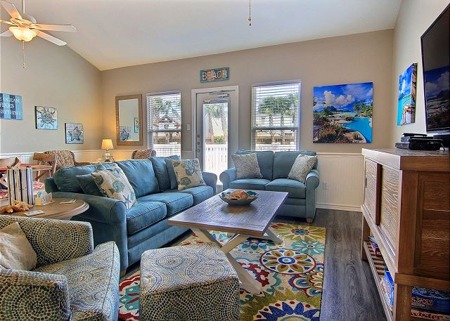 The living area has a Large flat screen for entertainment and windows with a view of the back patio