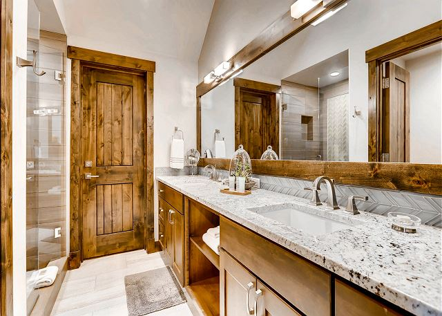 ensuite bathroom with shower and dual sinks
