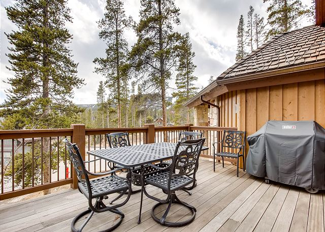 Upper level deck off living area with gas grill and additional outdoor dining