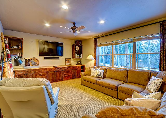 with large TV, Sonos music system, game table, and large comfy sectional couch