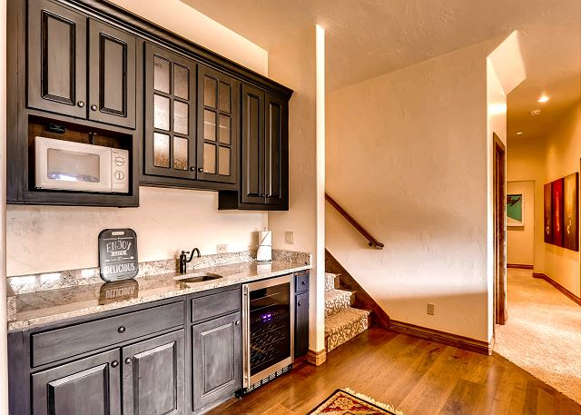 Lower level wet bar for entertaining off the spacious den with shuffle board