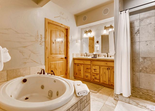 ensuite bathroom with dual sinks, walk-in shower and jetted tub