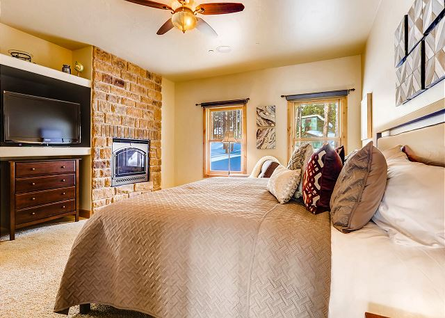 features a TV, warm fireplace, and large king bed