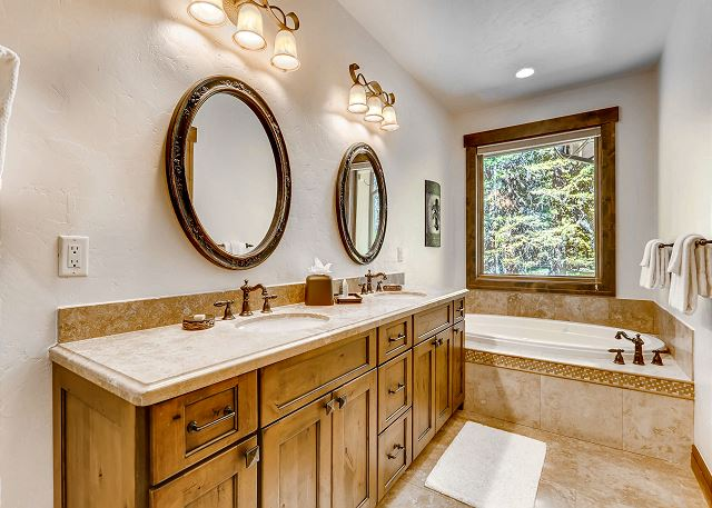 bathroom with dual sinks and large soaking tub