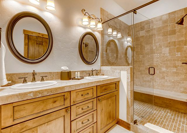 bathroom with shower and dual sinks