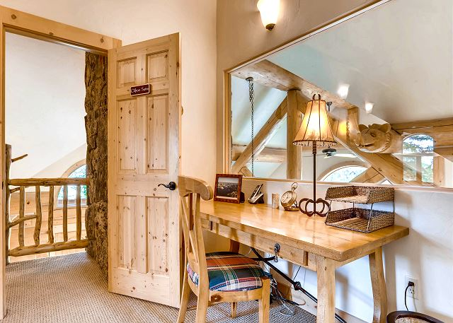 Study which overlooks the massive living room fireplace and hand carved decorative beams