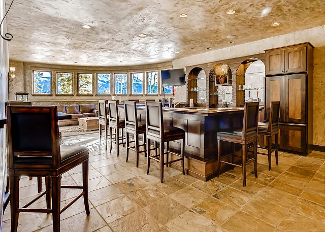 features a full bar, full sized refrigerator, 2 TV's, sitting area with sofa and arm chairs and billiards table