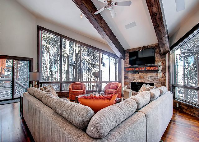Great Room features gas fireplace, TV, cozy seating and floor to ceiling windows