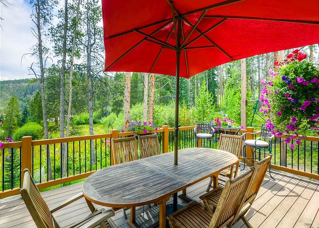 Deck in the Summertime with beautiful flowers and outdoor dining space