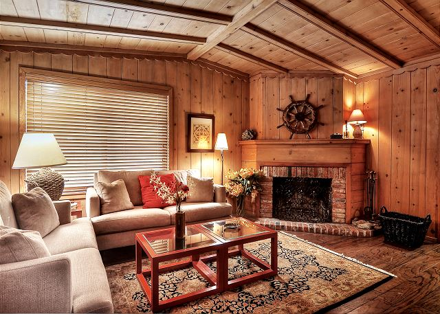 Living room features a high-vaulted ceiling & a wood-burning fir