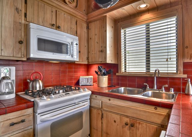 Fully stocked kitchen has a refrigerator, stove, microwave, cook