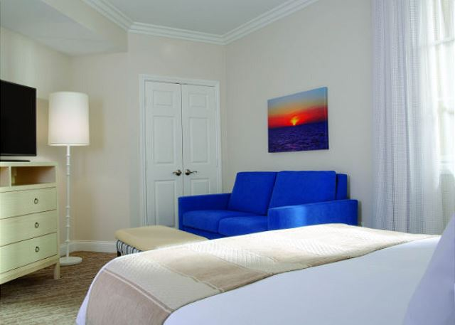 The master suite features a king-size bed, couch and TV