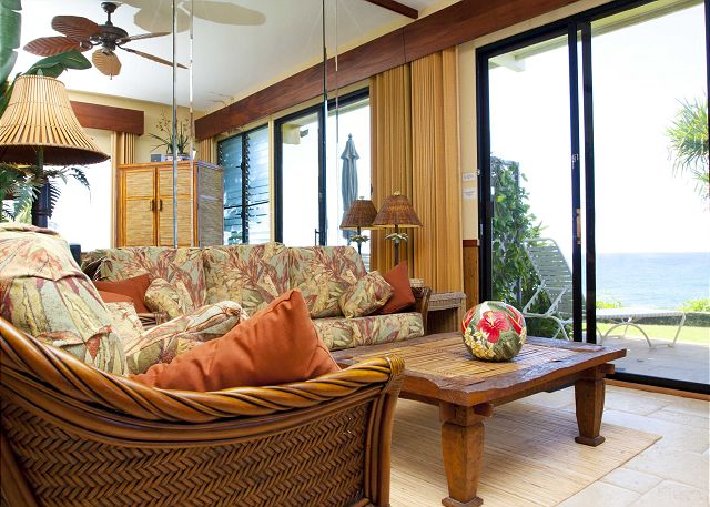 Beautifully furnished and appointed oceanfront living room that opens onto the grassy lawn.  Enjoy the birds playing and singing in the beautiful LauHala tree just outside the patio.