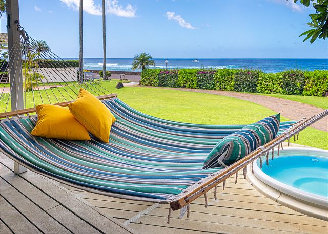 Koa Cottage's front lanai views from the hammock include the hot tub, manicured front yard, alternating privacy hedge and blue Pacific water.