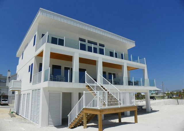 The gulf side of the home offers two levels of large deck space and stairs leading