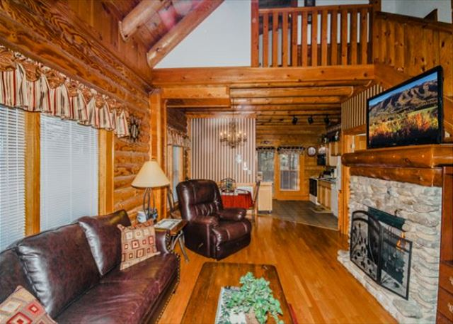 Spacious living room with seasonal fireplace, leather recliner and couch.
