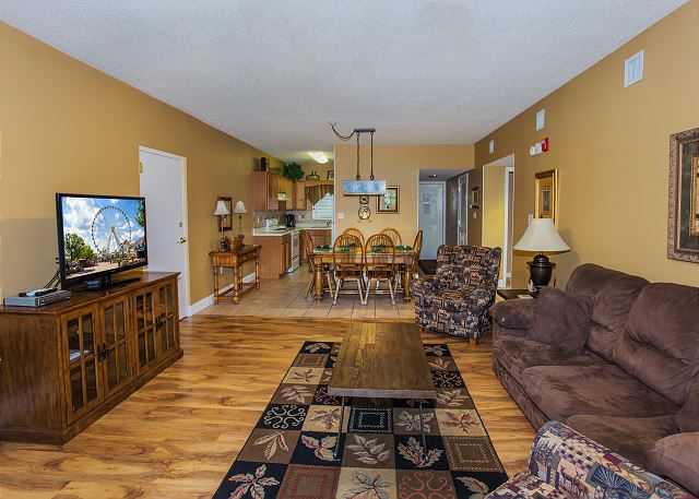 Hardwood floors with flat screen t.v. and a queen sleeper sofa.