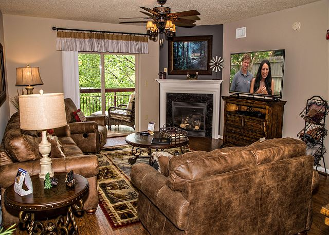 Comfortable Living Room with Hardwood Floor, Large Flat Screen TV, Ceiling Fan and Seasonal Gas Fireplace