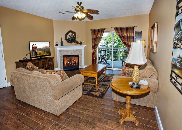 Living Room Has Hardwood floors with ceiling fan, flat screen t.v. and seasonal gas fireplace.