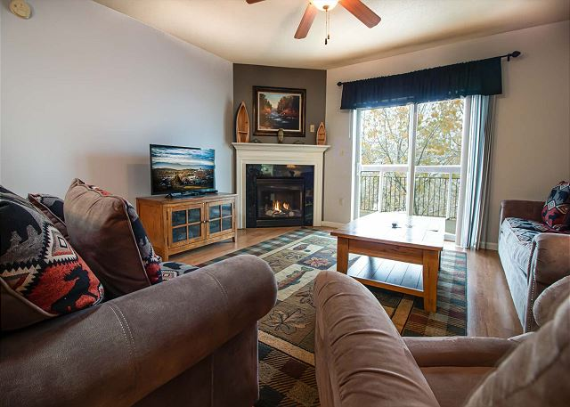 Living Room with spacious seating, seasonal fireplace, flat screen TV.