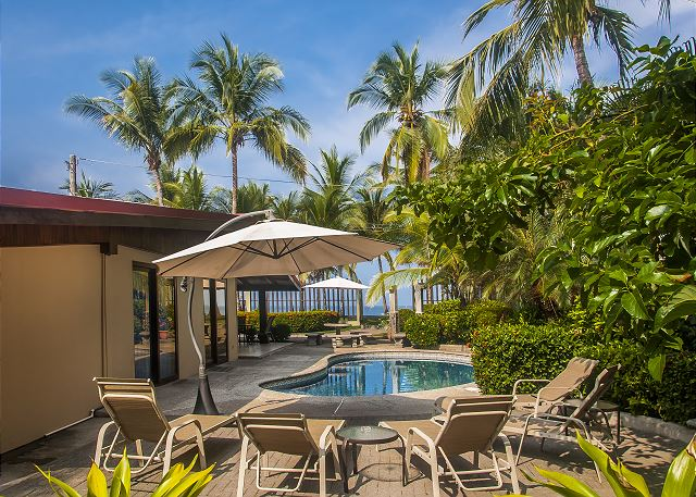 Pool area with charcoal grill, table, lounge chairs and umbrellas at Casa Mandolina vacation rental on the beach in Jaco Costa Rica