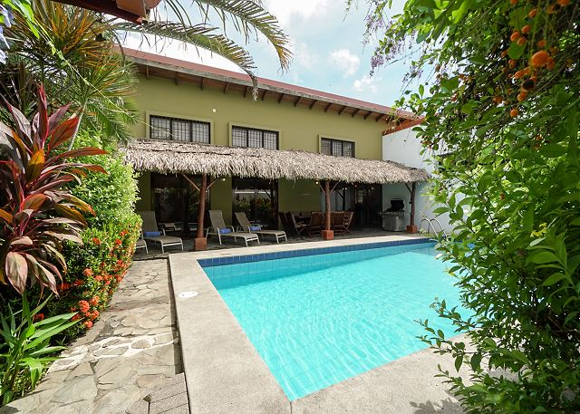 Pool area with palm thatched gazebo, table for 10 guests, gas grill at lounge chairs at Casa Gris vacation rental house near the beach in Jaco, Costa Rica