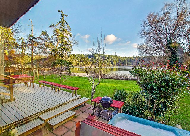 The sunny deck leads right down to the yard, the shore, and the hot tub and is also equipped with a charcoal grill for BBQing.