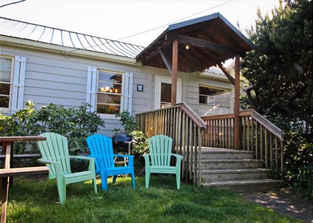 Large grassy fenced yard with covered entry deck, picnic table, charcoal BBQ and outdoor chairs.