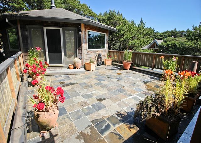 Upper south facing stone deck with gated stairs, charcoal BBQ and a patio table for 6.