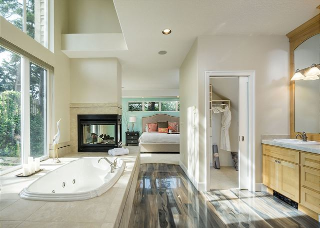 Master bathroom with soaking tub, double vanity, and walk-in closet