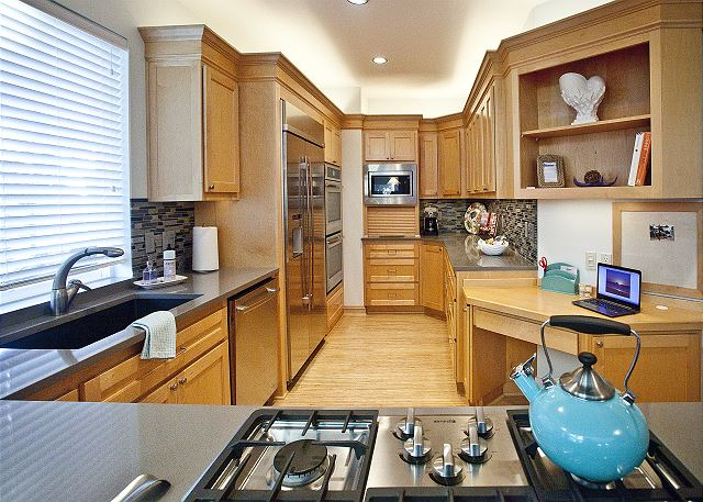 Professional grade stainless steel appliances including a double oven, 5 burner gas cooktop, and small appliance garage.