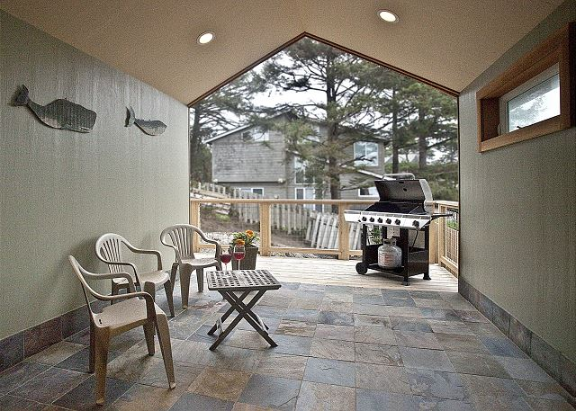 covered patio facing east provides a protected area for year-round grilling