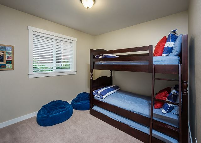 The downstairs bunk room with three twin beds and a flat screen TV - a kids favorite!