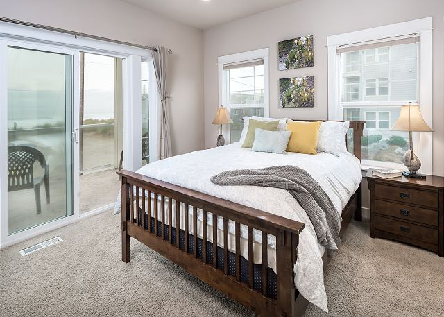 Luxurious master suite with queen bed and private balcony. End unit provides extra windows for exceptional views and light.
