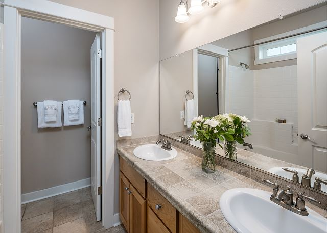 Double vanities, oversized mirror, and a jetted soaking tub in the master bath