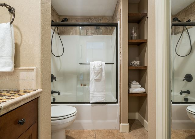 En suite bathroom with clever shelving and a shower/tub enclosure
