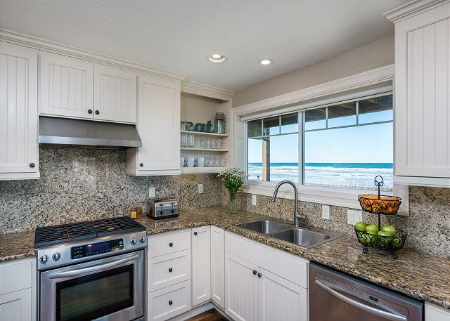 The full kitchen with granite slab counters includes a range of cooking equipment