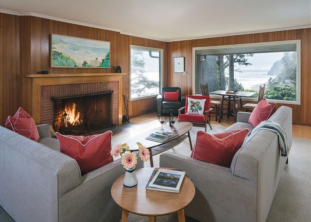 The living room with its wood paneling and statement fireplace is the perfect complement to the tree-framed ocean views