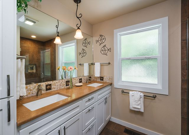 Master bath with double sinks and plenty of space for sunscreen and aloe in the ample cabinets