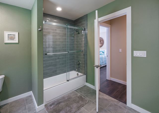Plenty of natural and overhead lighting in this guest bathroom with a shower/tub combo